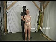 Masked man in dark suit ties brunette