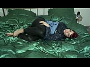 girl in shiny nylon rainwear playing on the bed