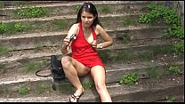 Red dressed girl in a public park .