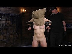 Brunette slave Cadence Luxe with bag on her head bound in metal device gets hard whipped