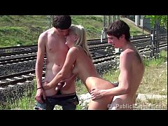 A guy is jerking off on his friend's gf in public by a railroad