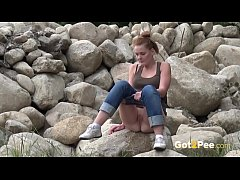 HD Redhead Pissing - A sexy European babe pees over rocks while outside