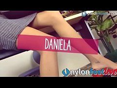 Daniela, a sexy brunette with the longest legs ever, wearing an elegant dress dangles her red pumps to show off her feet in tan pantyhose (NylonFeetLove.com)
