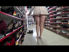 Voyeur and foot fetish in a public place. Beautiful legs in stockings and a juicy ass under a short dress in a shoe store.