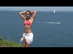 Chick in bikini strips by cliff