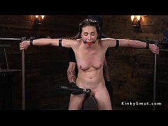 Brunette slave locked in metal device bondage with gag ball in mouth