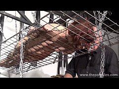 Redhead amateur slavegirl Bembys metal bondage lowered over burning candles and