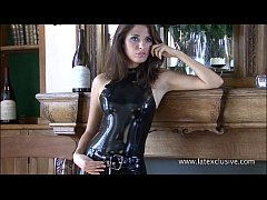 Shiny black latex outfit and fetishwear of sexy cougar Olivia posing in tight pl