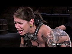 Brunette slave bound in metal device with dildo shoved in her pussy gets hard whipped