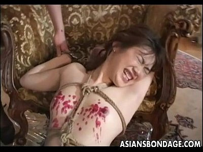 Naughty Asian babe tied up and drenched in hot wax