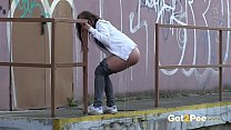 Brunette pushes her ass in the air to piss