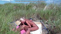 A couple of nudism lovers hardly pairing off on the sand Vorschaubild