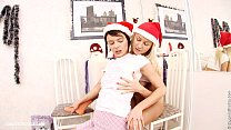 Christmas lesbians have fun with a red dildo on...