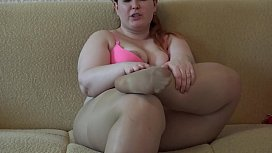 A fat girl in pantyhose licking her legs and masturbating