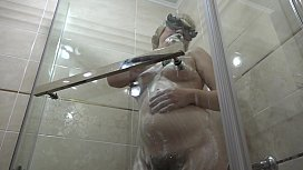 Pregnant milf in the lather in the shower masturbates with a dildo. Rubber dick fucks hairy pussy.