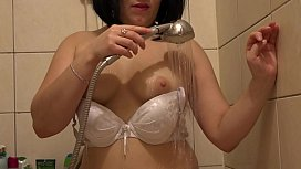 The brunette in the shower stall let down her wet panties and fucked her hairy pussy with a bottle.