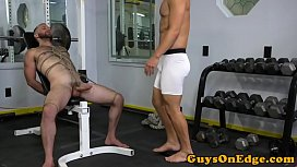 BDSM doms share restrained subs cock in gym