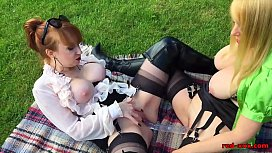 Red and her girlfriend play with a double dildo outside