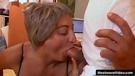 Grandson licks his grandmother'_s tits then picks up granny to the desk spreading her sexy legs and has intense sex with this old slut