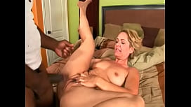 An experienced housewife caresses her wet pussy on the bed, and then fucks with a big black guy in all positions