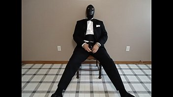 Seated in a tuxedo wearing a rubber cock and ball sheath and playing with my cock until I cum.
