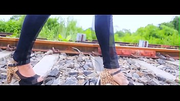 girl walking in heels on rail track