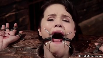 Little brunette slave Yhivi with wrists and head in wodden stock gets mouth banged through spider gag then anal rough banged by huge dick master