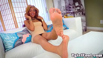 Footworshipping shemale plays with her feet