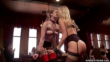 Bound slaves kissing at orgy party