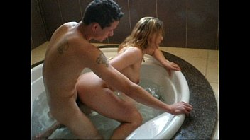 blonde giving to another in the bathtub