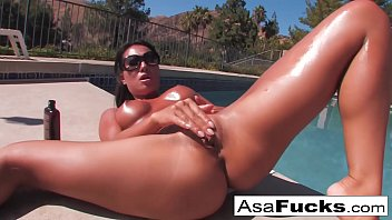 Asa  lays out by her pool and gets oiled up