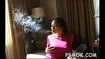 Horny babe smoking while giving a blowjob to her stud