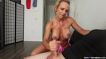 Milf kenzie Foxx fresh out the shower wearing a pink towel gives a handjob to a man jerking off on the couch.