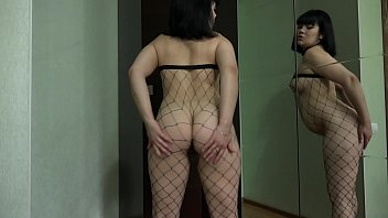 A cute brunette with an appetizing round tummy, in a sexy suit, masturbates a hairy pussy in front of a mirror.