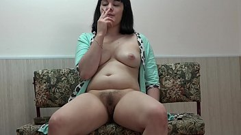 The brunette smokes a cigarette and masturbates her hairy pussy. Homemade fetish and vagina fingering.