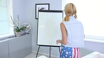 Cameraman shoots a blonde in glasses writing on the white board