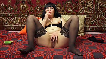 A brunette in stockings smokes a cigarette and masturbates her hairy pussy. Close-up of a wet hole with orgasm juices. Fetish.