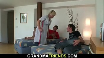 Two young dudes share old blonde cleaning woman