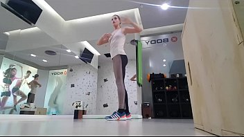 Cute blonde teen doing warmup at the gym