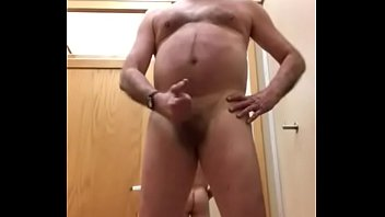 A daddy getting naked and trying on a pair of pants in a clothing store dressing room.