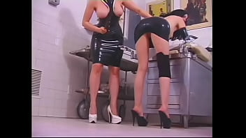 Redhead Milf in latex dress spanks young brunette m blindfold on the ass