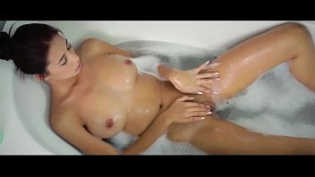 Busty babe plays with her shaved pussy in the bath