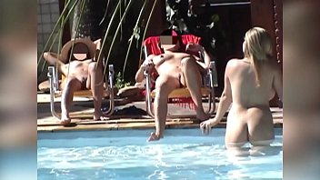 Girl pretends to be using her cell phone to film a group of naked friends in the pool