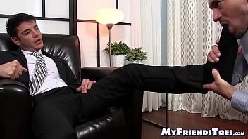 Handsome businessman strokes cock while his feet are licked