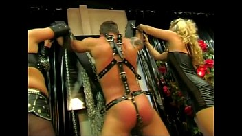 Two mistresses whipping their slave