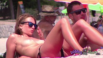 Ice Cool Blonde Babe sunbathing topless on the beach