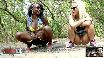 Two girlfriends peeing together in the woods