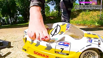 Kati´s bare foot crushing a large DTM racing car bare foot and with her ballerinas