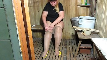 A young bbw with a big ass in nylon pantyhose drowns the stove in a rustic Russian bath.