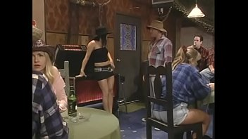 Red-haired guy fucks a slutty brunette in a cowboy hat in front of the visitors of the bar